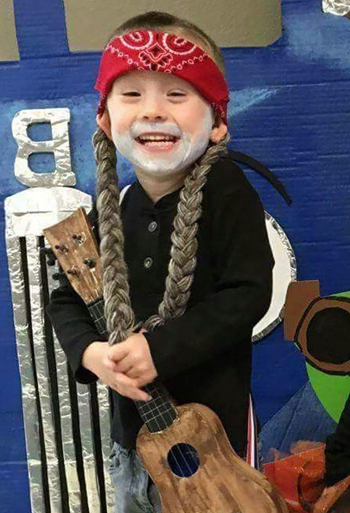 little boy, dressed as willie nelson, holding a guitar, funny halloween costumes for kids, two braids, red bandana
