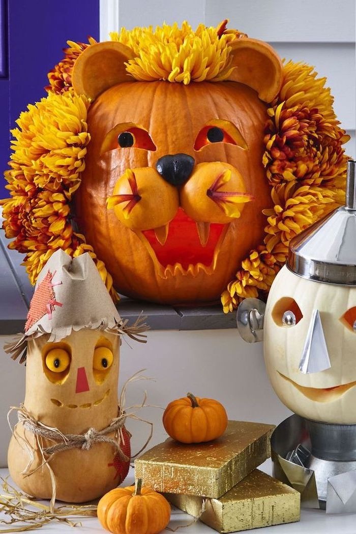 wizard of oz characters, carved into pumpkins, halloween pumpkin carvings, arranged on a patio