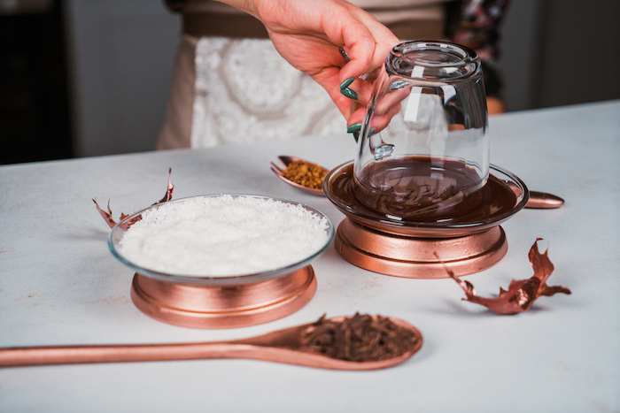 glass jar dipped into melted chocolate, coconut shavings in another bowl, homemade hot chocolate recipe, placed on white surface