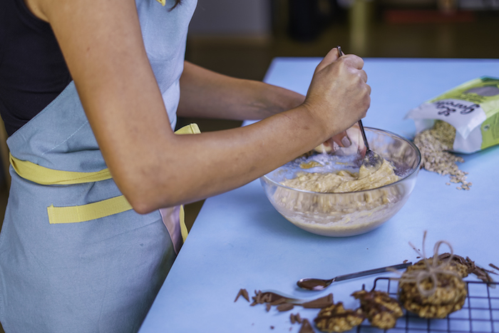 woman stirring mix, in a glass bowl, on a blue table, wearing a blue apron, chocolate chip cookies, oatmeal on the table