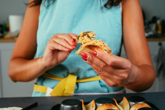 woman with red nail polish, filling tortilla wraps, taco meat recipe, brass spoon, blue apron