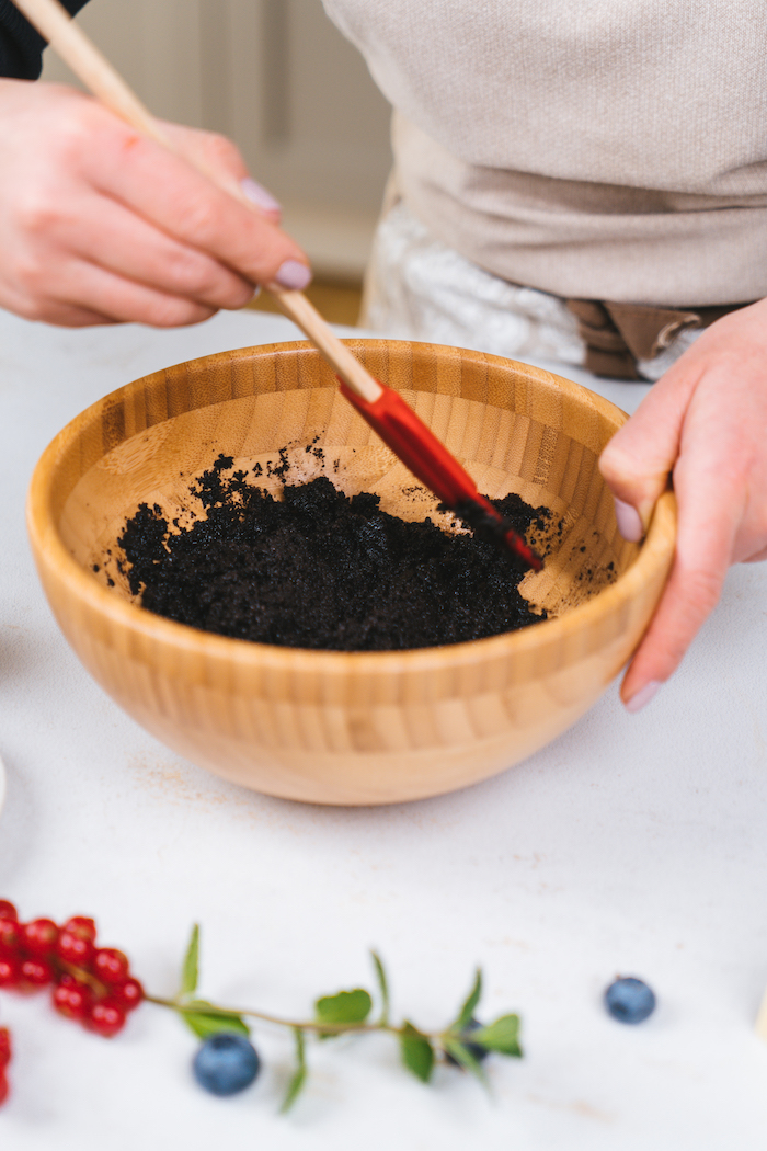 oreo crumbs, mixed with red spatula in wooden bowl, placed on white table, no bake oreo cheesecake