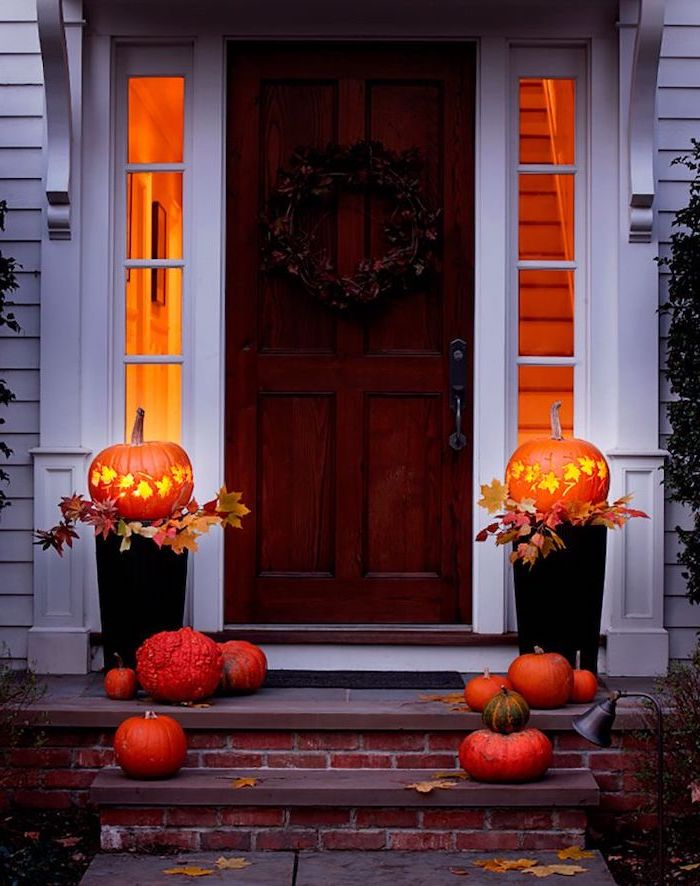 two pumpkins, lit by candles, smaller pumpkins, arranged on stairs, in front of a door, halloween pumpkin carvings