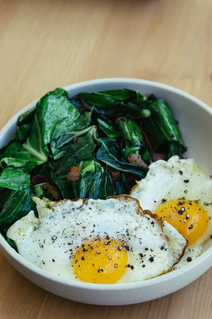 spinach and bacon, on the side, fried eggs, in a white bowl, easy keto meals, wooden table