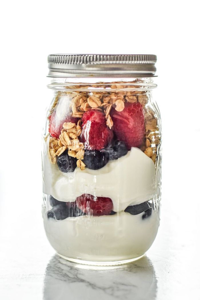 mason jar, filled with granola and yoghurt, raspberries and blueberries, meal prep, white background