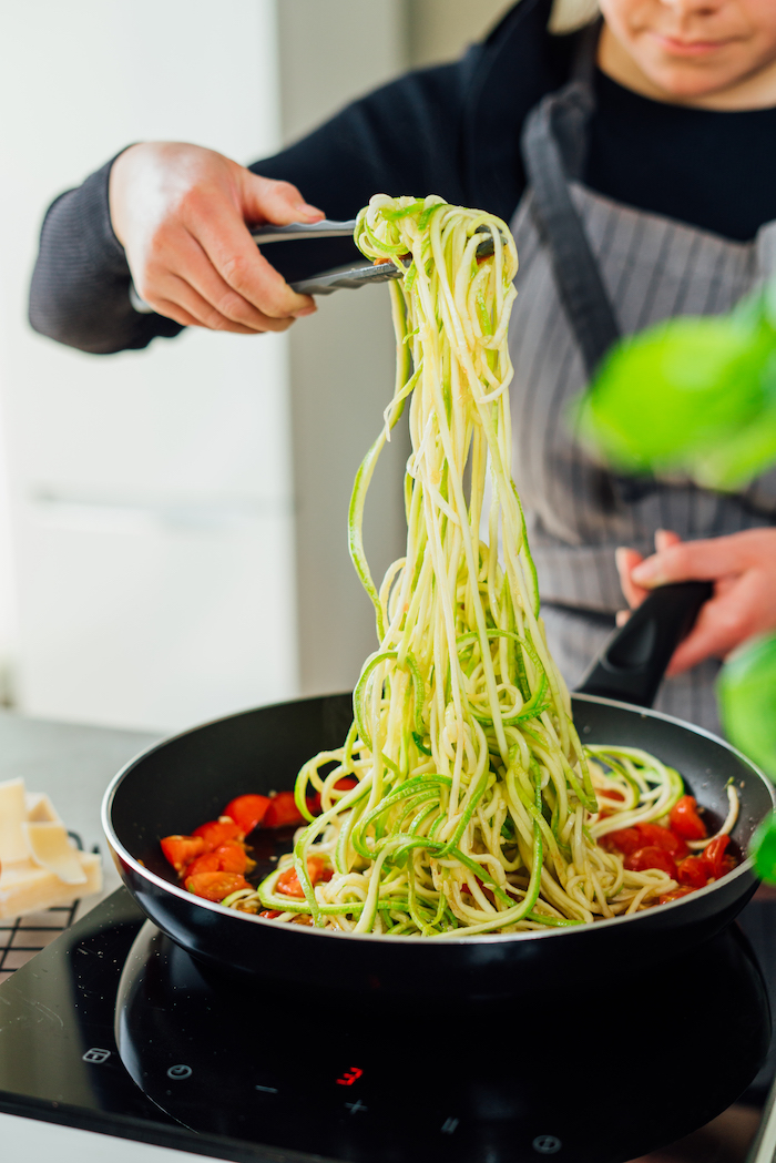 zoodles added to cooked cherry tomatoes in saucepan how to make zoodles being cooked with tongs