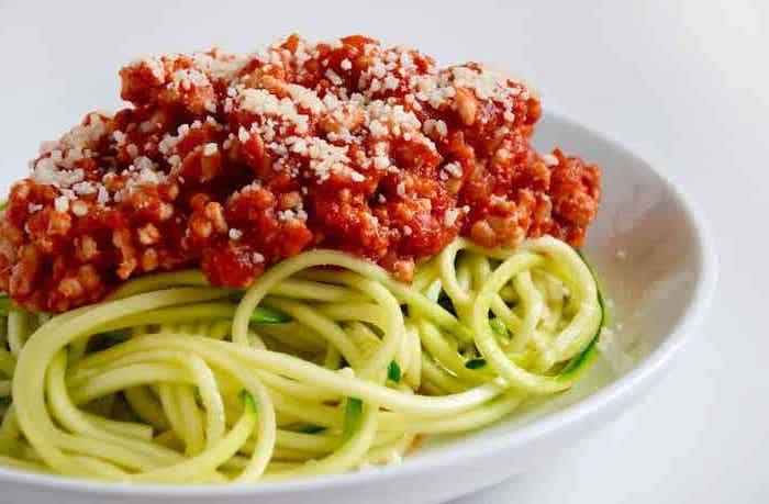 zucchini noodles, turkey bolognese, parmesan on top, what are zoodles, white plate, white background