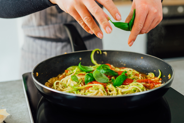 zucchini noodles being cooked with halved cherry tomatoes fresh basil leaves in saucepan