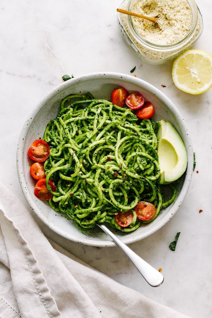zoodles with pesto, making zucchini noodles, cherry tomatoes, avocado slice, ceramic bowl, white cloth