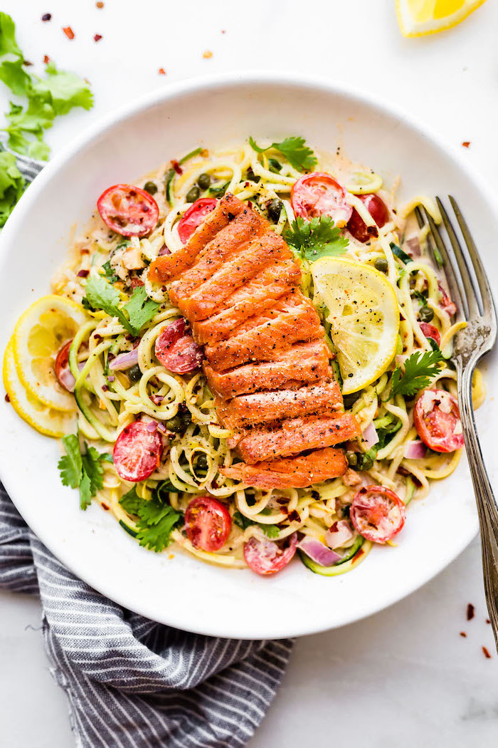 salmon on top, zoodles with sauce, cherry tomatoes, making zucchini noodles, white plate, silver fork