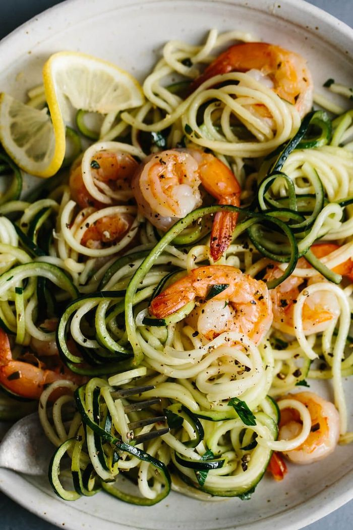 shrimp zoodles, in a white plate, lemon slice on the side, zucchini noodles spaghetti