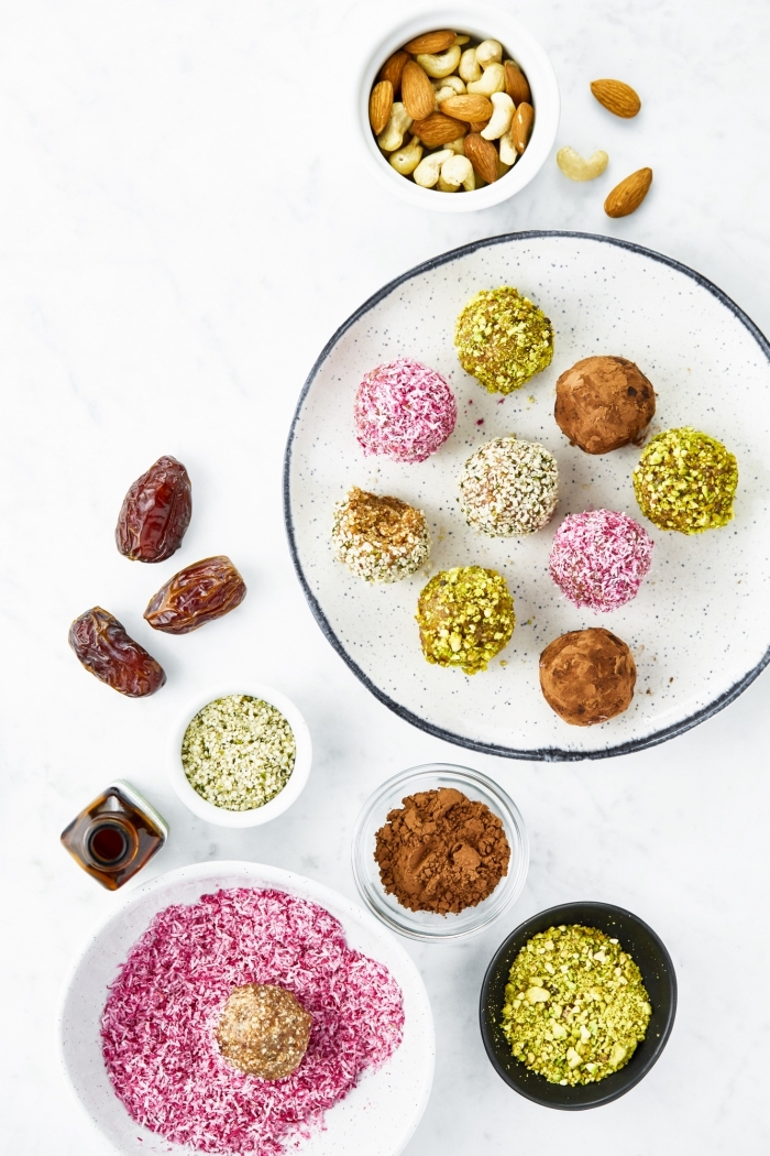 almonds and dates, cocoa and pistachio nuts, no bake energy bites, in bowls, white table