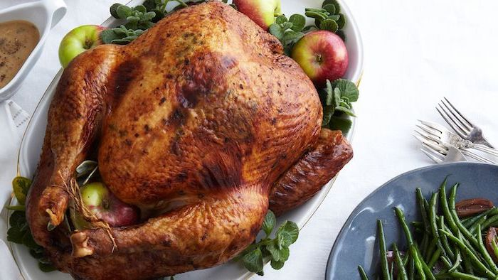roasted turkey, fresh herbs, apples on the side, how to bake a turkey, white table, gravy in a jug