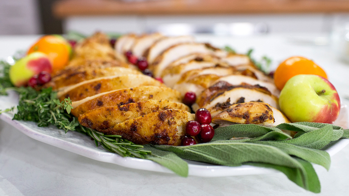 turkey slices, fresh herbs, apples and tangerines, cranberries on the side, how to bake a turkey, white plate