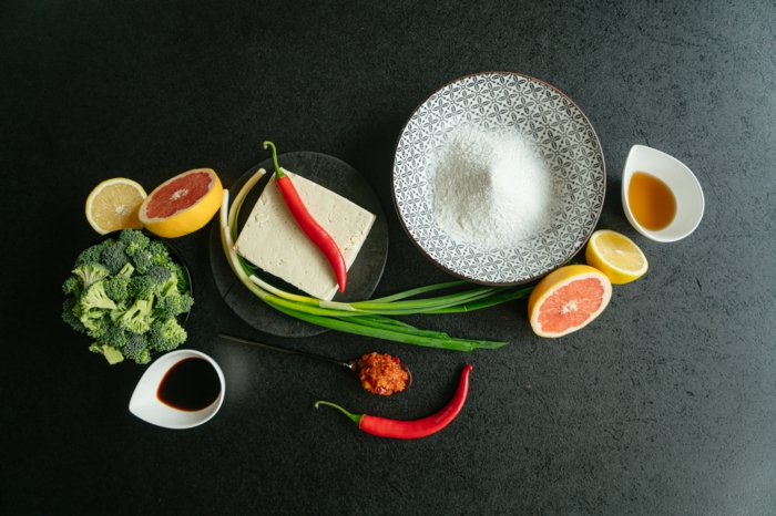 asian tofu, grapefruits and lemons, broccoli and soy sauce, ingredients spread on black countertop