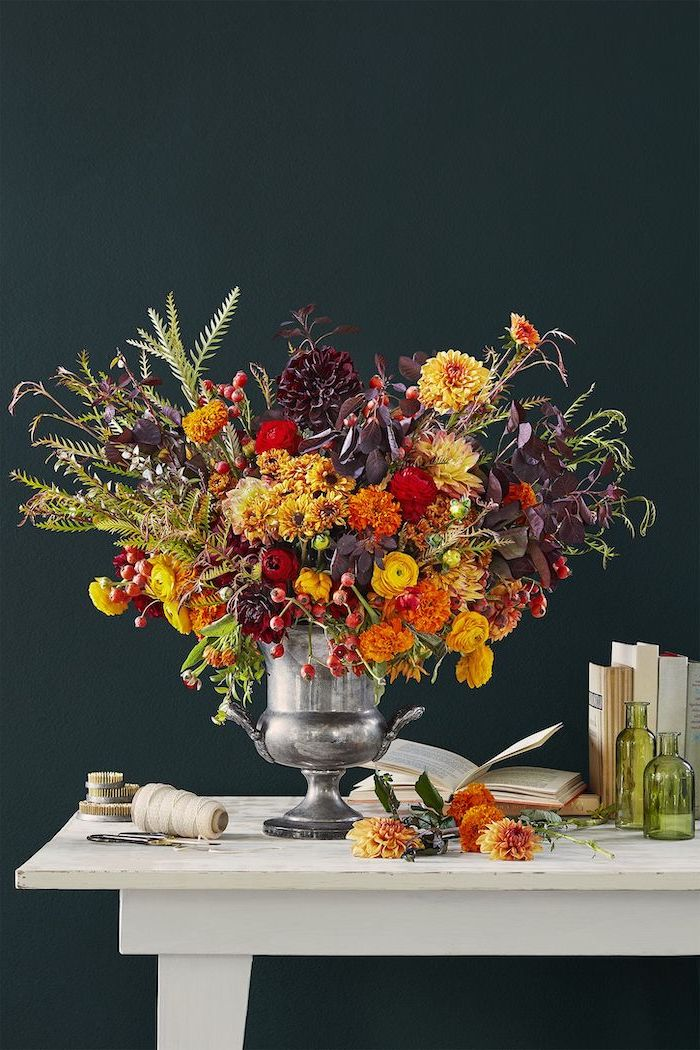 large bouquet, made of autumn flowers, in large silver vase, thanksgiving decorations, black background