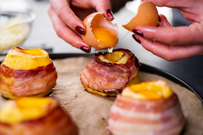 bacon slices wrapped around halved potatoes, baked potato volcanoes, filled with eggs, arranged on paper lined sheet pan