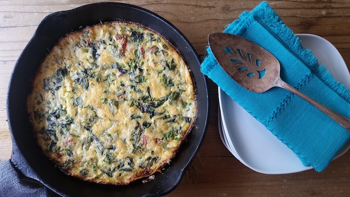 baked frittata, in black skillet, weeknight dinners, white plates, blue cloth, wooden table, metal spatula