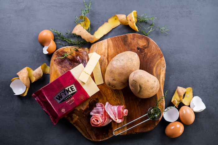 ingredients arranged on wooden board, baked potato volcanoes, potatoes bacon and cheese, placed on black surface
