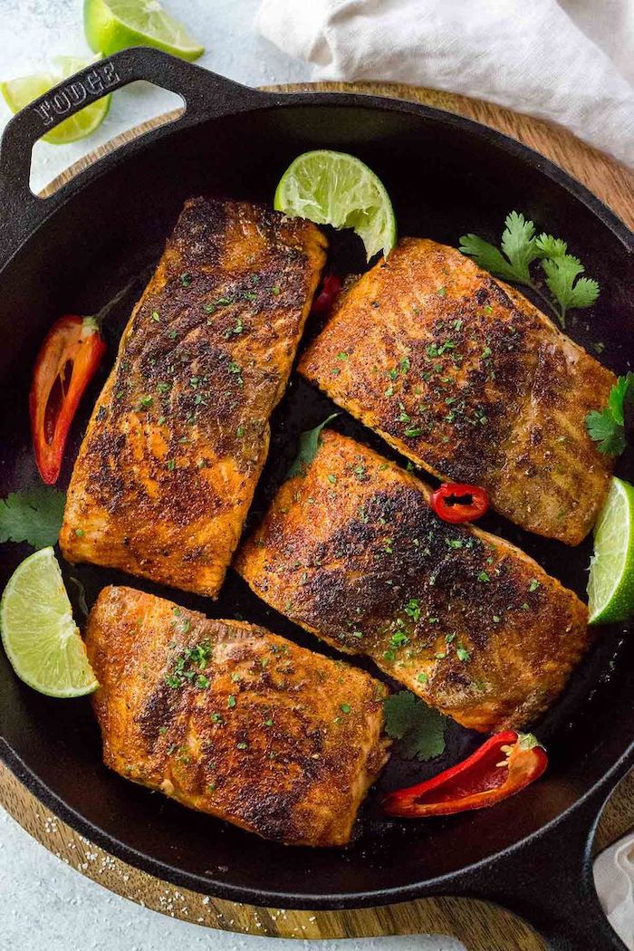 baked salmon, in a black skillet, with sliced peppers, lime slices, low calorie meals, parsley garnish