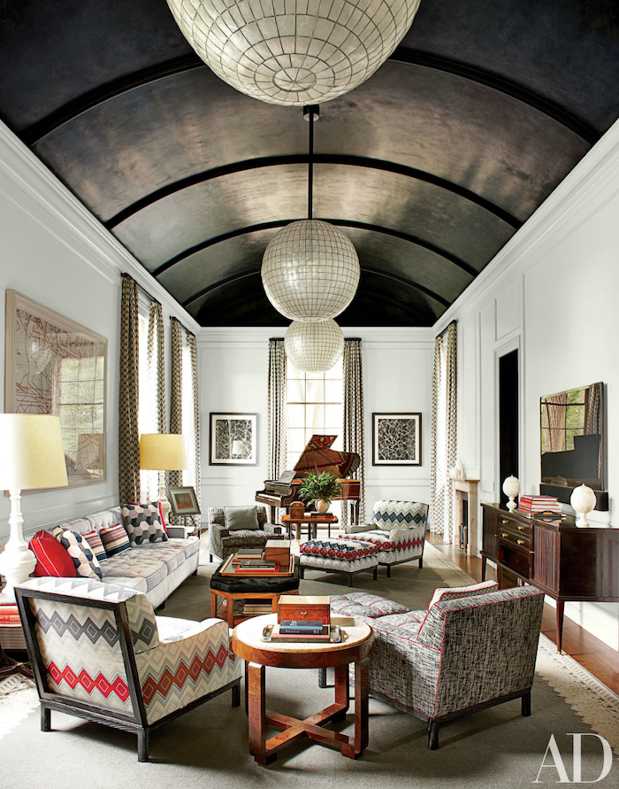 vaulted ceiling, barrel ceiling, colorful printed armchairs, wooden floor, large grey carpet, white walls