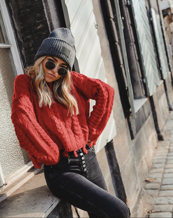 medium length hairstyles for women, woman leaning on wall, wearing black jeans, red sweater, grey beanie and sunglasses