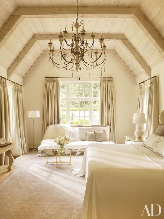 beige bedroom, wooden ceiling, vaulted ceiling, beige curtains, white sofa, hanging chandelier