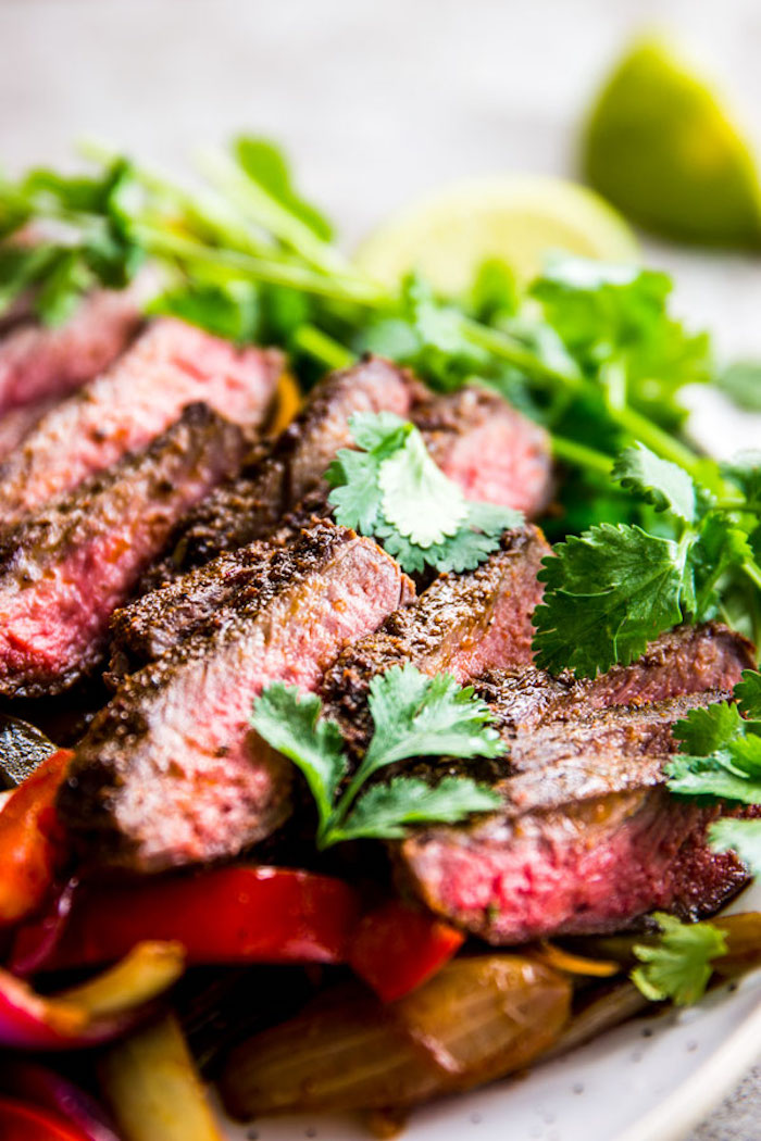 steak fajitas, sliced peppers, parsley garnish, low calorie meals, white plate, blurred background