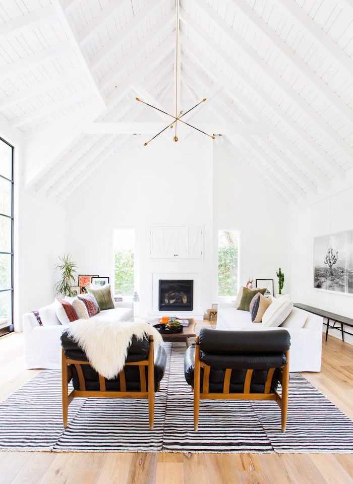 black leather armchairs, white sofas, black and white carpet, vaulted ceiling, wooden floor