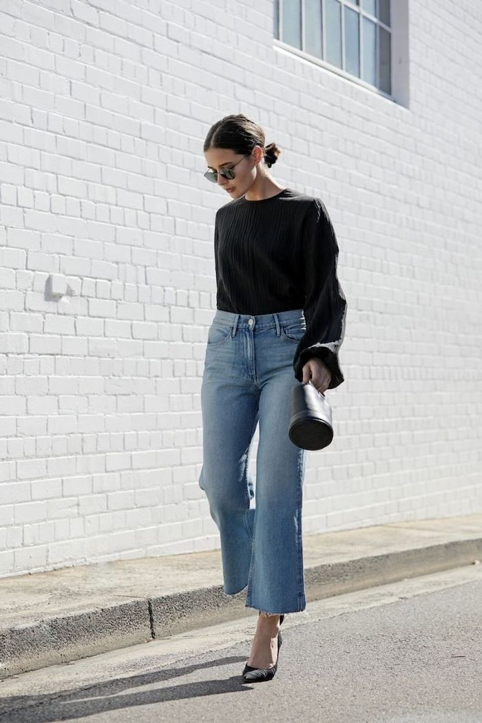 woman walking down the street, wearing black blouse and jeans, medium length hairstyles for women, carrying black bag