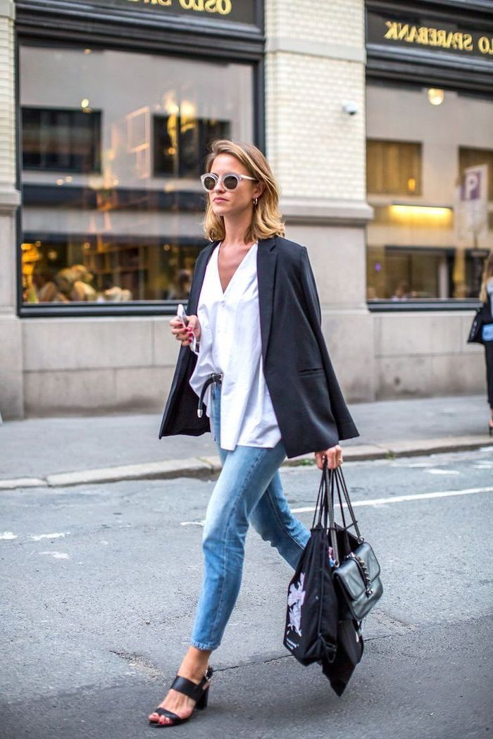 woman walking down the street, wearing jeans and white shirt, shoulder length hairstyles, blonde hair, holding bags