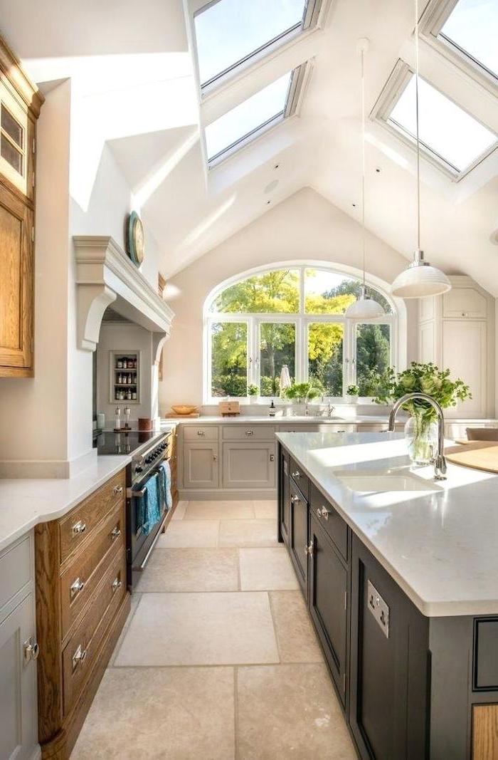 white ceiling with skylights, kitchen island, tiled floor, wooden cupboards, hanging lamp shades, what does vaulted mean