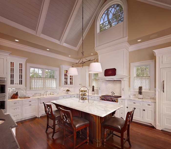 marble kitchen island, white cupboards, what does vaulted mean, wooden floor, wooden chairs