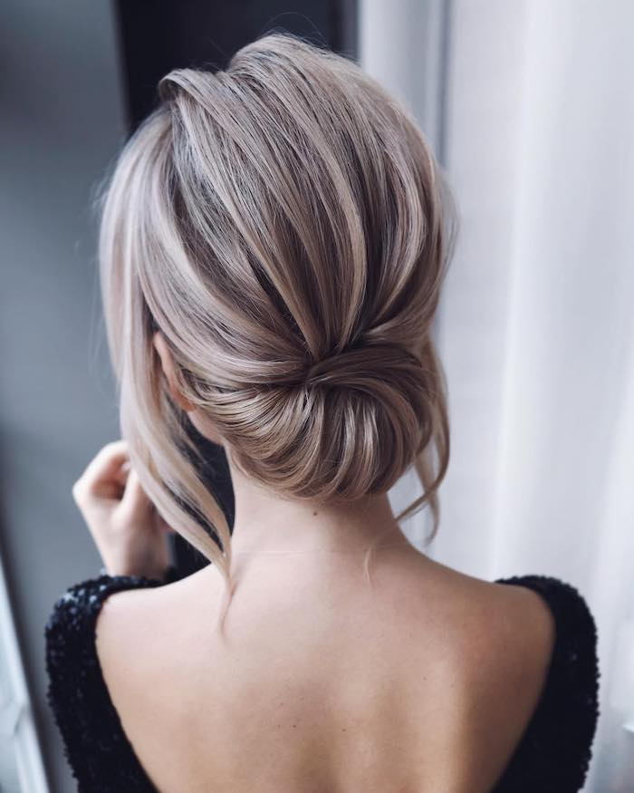 blonde hair in a low chignon, medium length hairstyles for women, woman wearing black sequinned dress