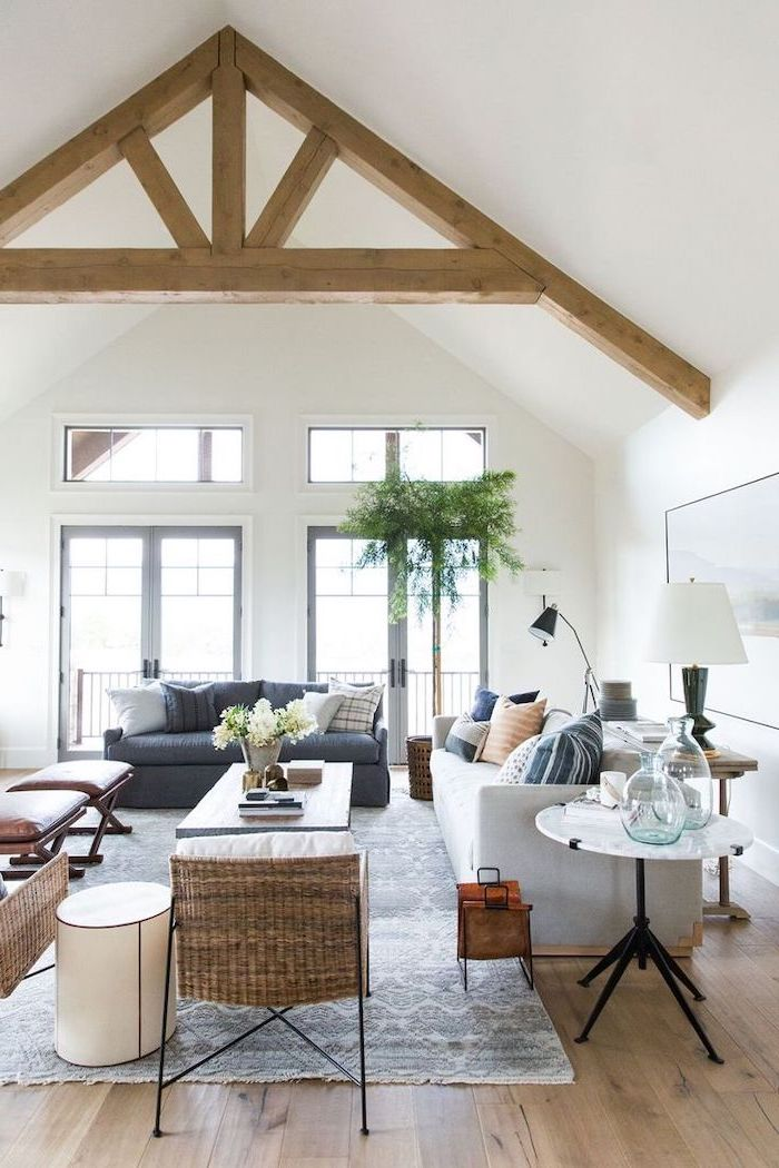 wooden floor, vaulted ceiling beams, white ceiling, white sofa, black leather sofa, blue carpet, tall windows