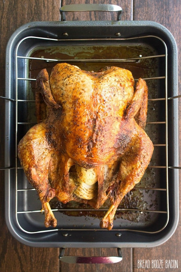 roasted turkey, on a railing, on black pan, thanksgiving turkey recipe, wooden table