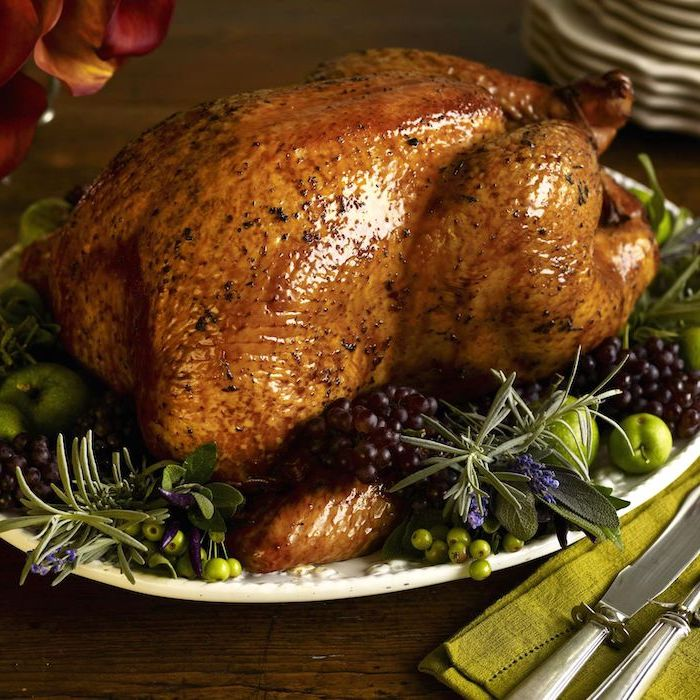 how to bake a turkey, roasted turkey, blackberries and apples, fresh herbs, on the side, wooden table, green cloth