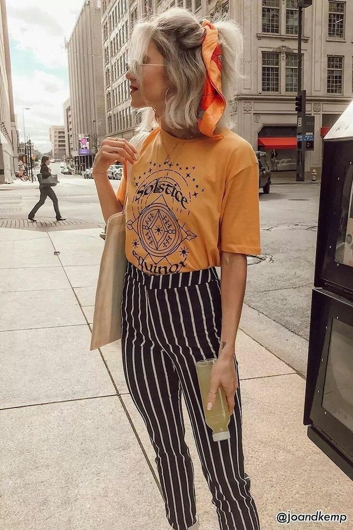 woman with blonde hair, half up tied with silk scarf, wearing orange t shirt, black and white striped pants, medium haircuts for women