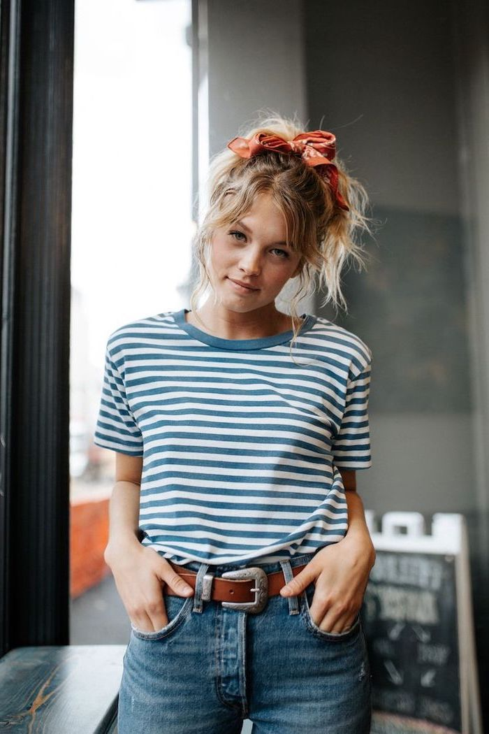 woman with curly blonde hair in a ponytail, tied with a bandana, medium haircuts for women, wearing blue and white t shirt and jeans