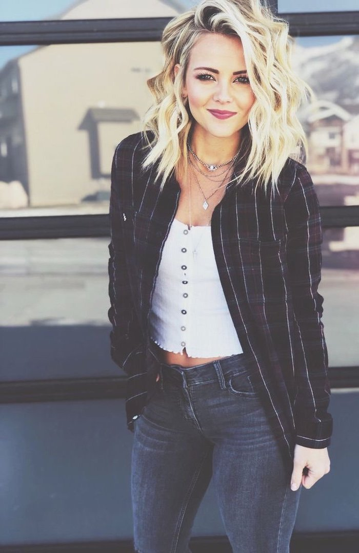 woman with wavy blonde hair, medium haircuts for women, wearing white top and jeans, black blazer
