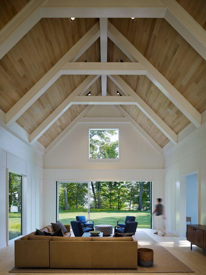 beige leather corner sofa, blue velvet armchairs, vaulted ceiling, tall windows, white beams