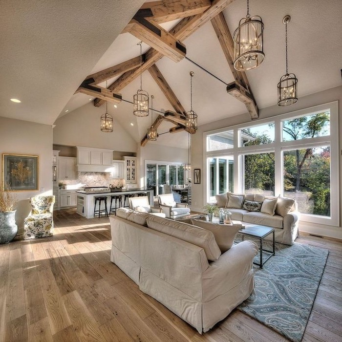 white sofas, wooden floor, blue carpet, hanging lamps, vaulted ceiling beams, kitchen island