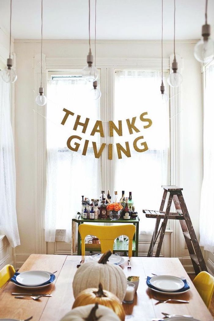 thanksgiving banner, turkey decoration, pumpkins arranged on table, plate settings, alcohol bar, wooden ladder