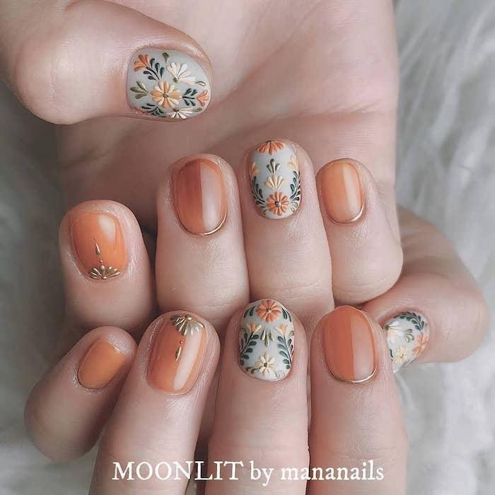 orange and grey nail polish, fall nail designs, floral designs, short squoval nails, white background