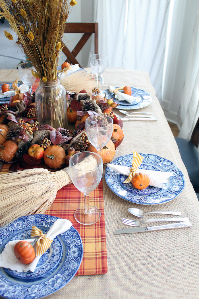 wreath made of pumpkins, pine cones, apples and leaves, thanksgiving decorations, blue plates, wine glasses