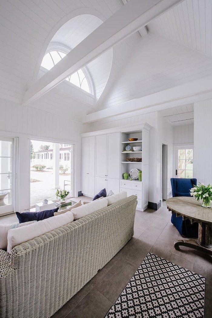 wooden floor, vault definition, white cupboard, blue velvet armchair, wooden table, blue throw pillows
