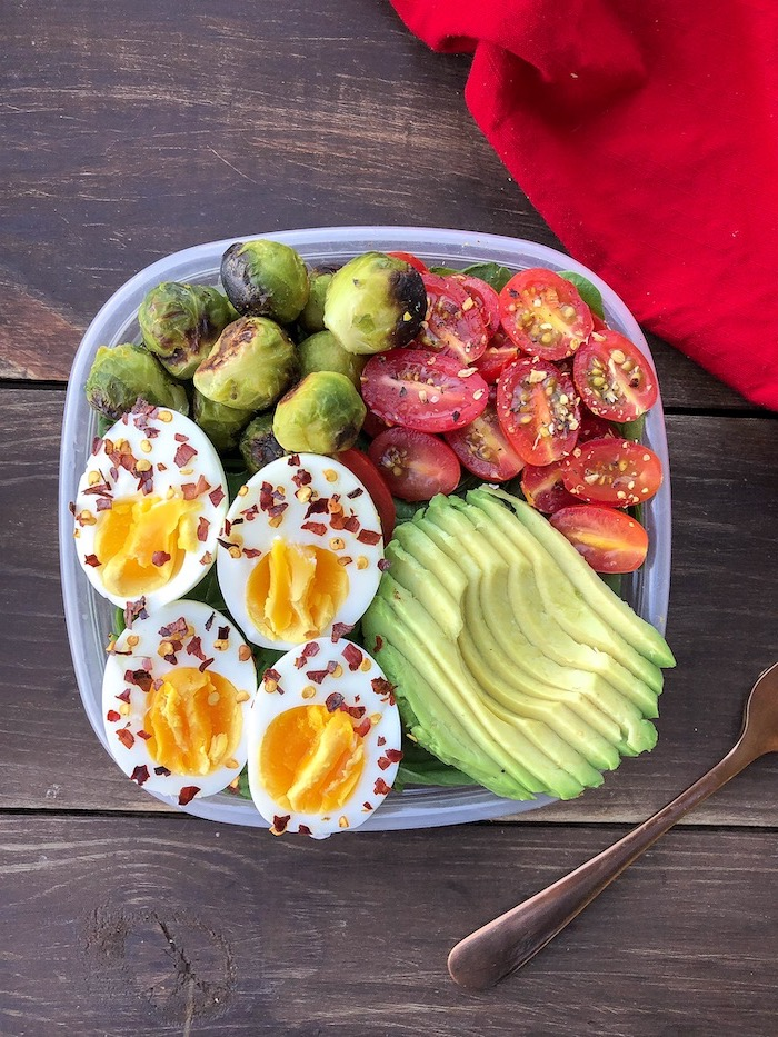 meal prep for weight loss, plastic container, filled with avocado, cherry tomatoes, boiled eggs, wooden table