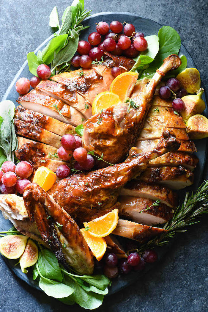 carved turkey, grapes and dragon fruit, fresh herbs, lemon slices, on the side, how to bake a turkey