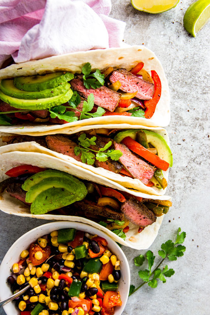 steak fajitas, weight loss diet, avocado slices, corn and peppers, cherry tomatoes, black beans, in a white bowl
