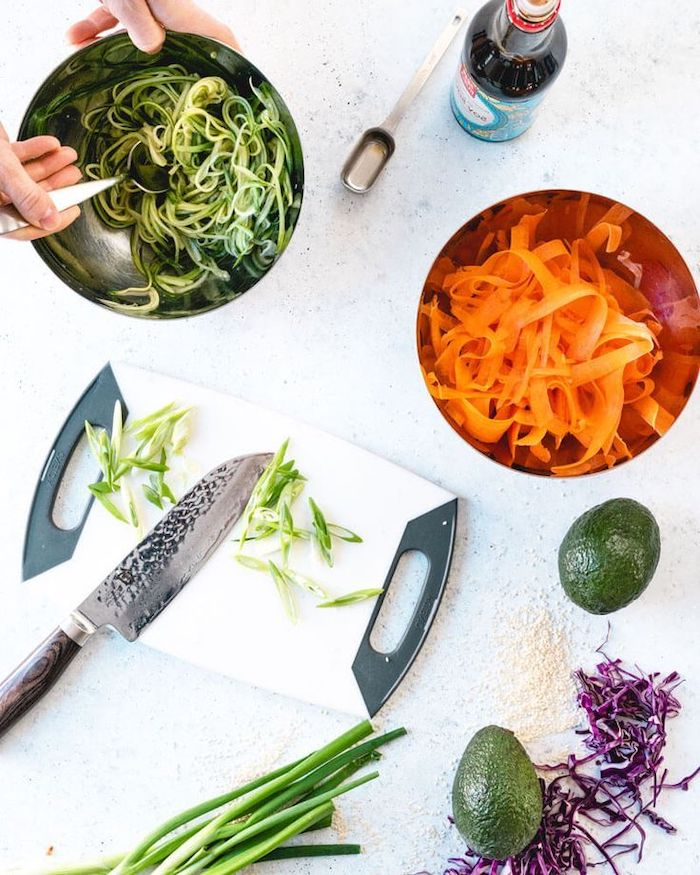 spiralised zucchini and carrots, in metal bowls, dinner ideas for tonight, white chopping board, white table, avocados and leeks